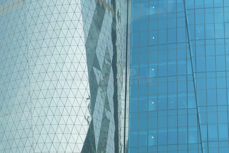 Las ventanas de la oficina en tonalidades del azul reflejan la luz en Doha imágenes de archivo libres de regalías