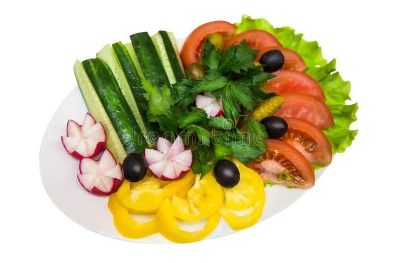 Las verduras cortadas frescas en la placa en blanco aislaron el fondo foto de archivo libre de regalías