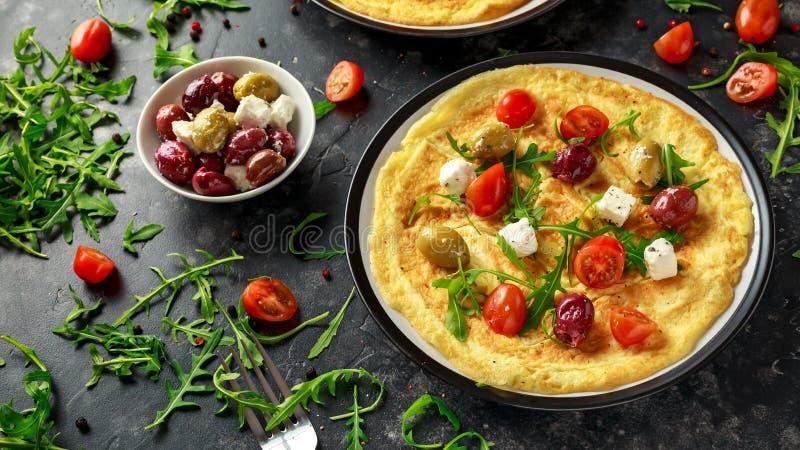 Las verduras Eggs la tortilla con los tomates, cohete salvaje, queso griego, aceitunas en una placa Comida sana del desayuno de l imagen de archivo