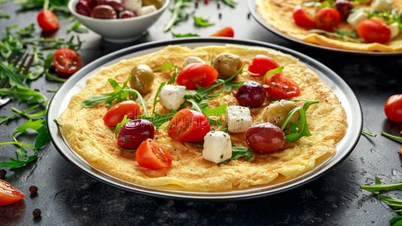 Las verduras Eggs la tortilla con los tomates, cohete salvaje, queso griego, aceitunas en una placa Comida sana del desayuno de l imagenes de archivo