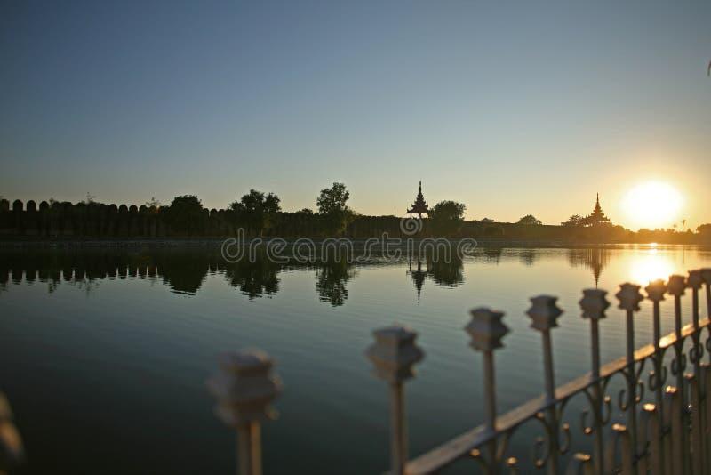 Las verjas de la cerca iluminadas en la puesta del sol detrás del fuerte de Mandalay, Birmania fotos de archivo