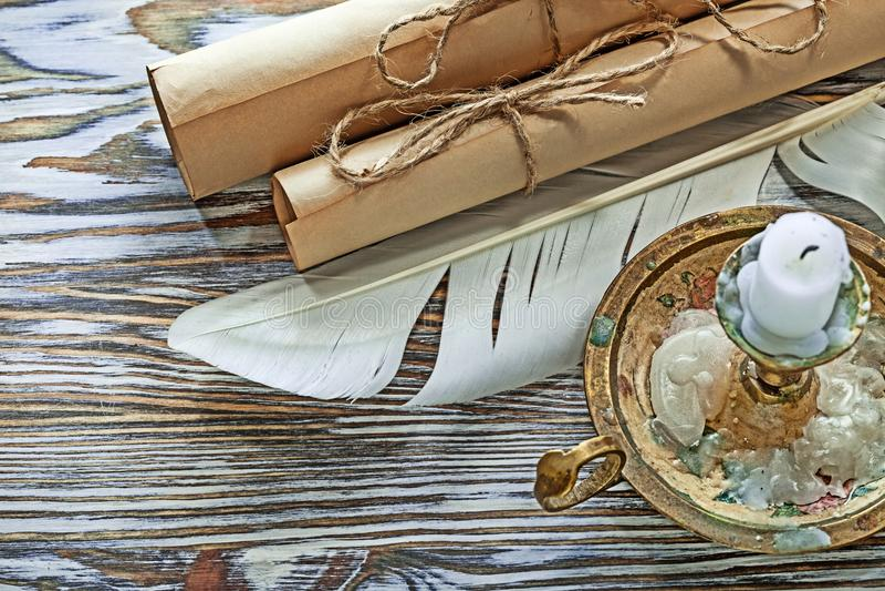 Las volutas de papel del vintage plume la vela del candelero en el tablero de madera imágenes de archivo libres de regalías