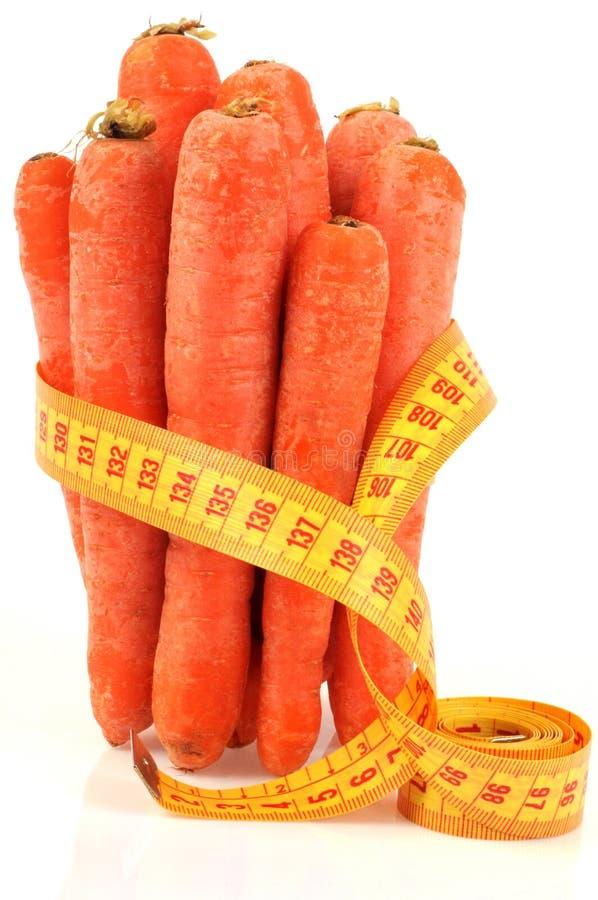 Las zanahorias crudas rodaron para arriba con un metro de la costurera en un fondo blanco imagenes de archivo