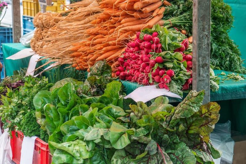 Las zanahorias frescas, el perejil y diversos tipos de lechuga se venden en el mercado del granjero en un día del otoño en cajas  imagenes de archivo