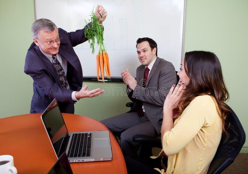 Las zanahorias que cuelgan del gran motivador fotos de archivo