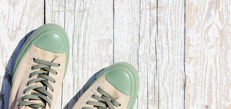 Las zapatillas de deporte atadas se colocan en un fondo de madera blanco Verano, opinión superior de zapatos de los deportes fotos de archivo