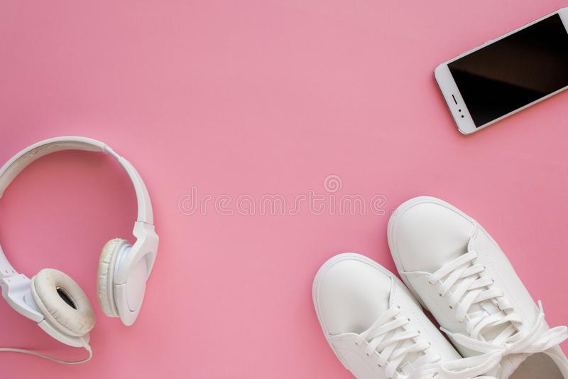 Las zapatillas de deporte blancas, auriculares, smartphone están mintiendo en un fondo rosado brillante fotografía de archivo