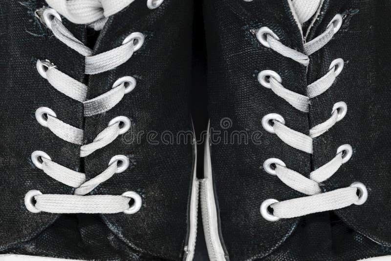 Las zapatillas de deporte negras, viejas y sucias con el fondo blanco del cordón emergen fotografía de archivo