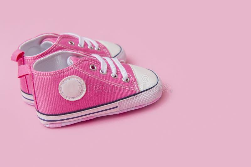 Las zapatillas de deporte rosadas lindas del bebé se cierran para arriba en fondo rosado fotos de archivo libres de regalías