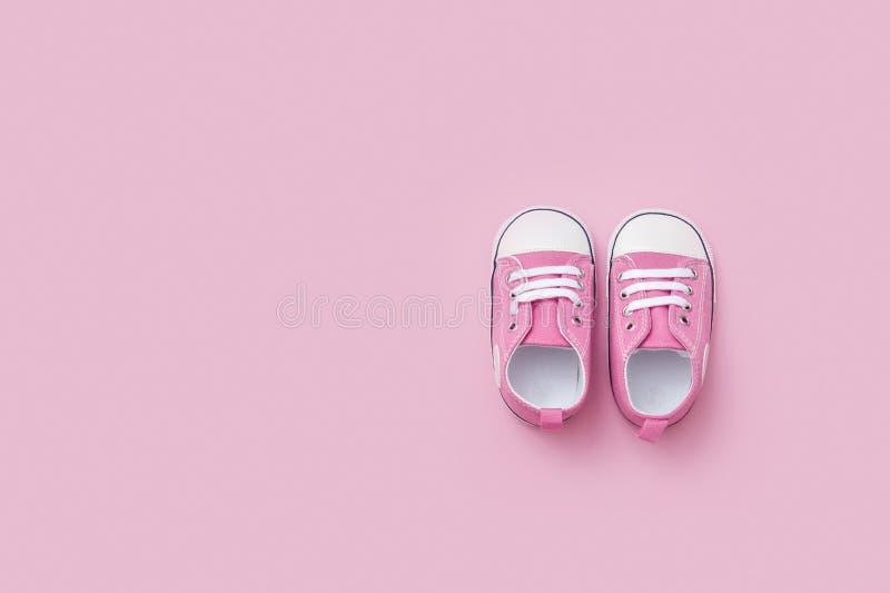 Las zapatillas de deporte rosadas lindas del bebé se cierran para arriba en fondo rosado fotografía de archivo