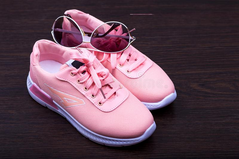 Las zapatillas de deporte rosadas de las mujeres en un fondo marrón puntos en un marco blanco Divi?rtase los zapatos Calzado de l imagen de archivo