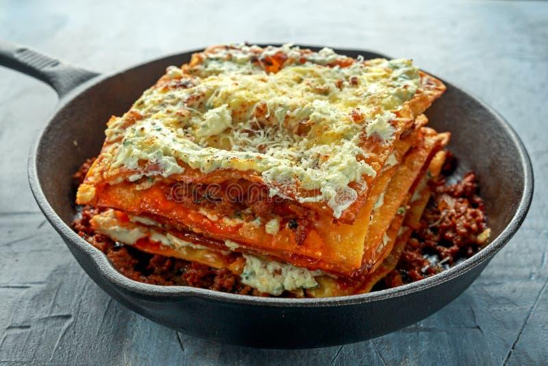 Lasañas curruscantes hechas en casa en cacerola del hierro con la salsa boloñesa de la carne de vaca picadita, queso parmesano fotos de archivo