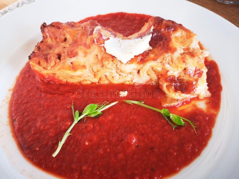 Lasañas en salsa de tomate Lasañas italianas deliciosas sabrosas del plato con la salsa y el queso cremoso de tomate con el salat imagen de archivo