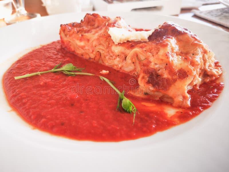 Lasañas en salsa de tomate Lasañas italianas deliciosas sabrosas del plato con la salsa y el queso cremoso de tomate con el salat foto de archivo