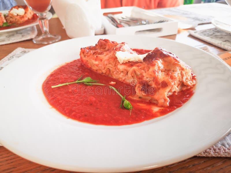Lasañas en salsa de tomate Lasañas italianas deliciosas sabrosas del plato con la salsa y el queso cremoso de tomate con el salat imagen de archivo libre de regalías