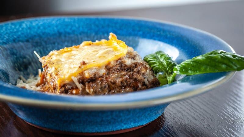 Lasañas italianas con la carne picadita boloñés, las zanahorias, y el queso parmesano en una placa azul de cerámica hermosa Copie foto de archivo