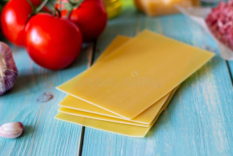 Lasa?as, tomates, carne picadita y otros ingredientes Fondo de madera azul Cocina italiana fotografía de archivo