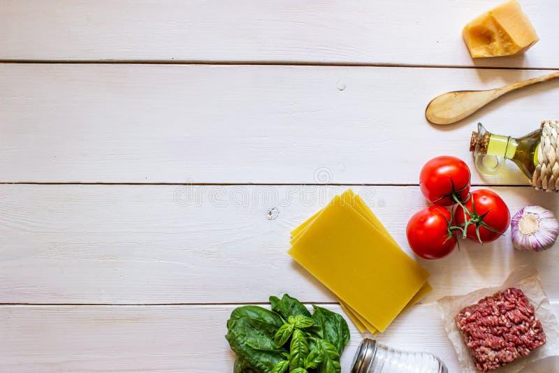 Lasa?as, tomates, carne picadita y otros ingredientes Fondo de madera blanco Cocina italiana imágenes de archivo libres de regalías