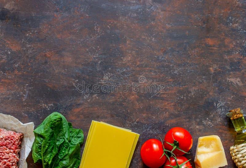 Lasa?as, tomates, carne picadita y otros ingredientes Fondo oscuro Cocina italiana imagen de archivo
