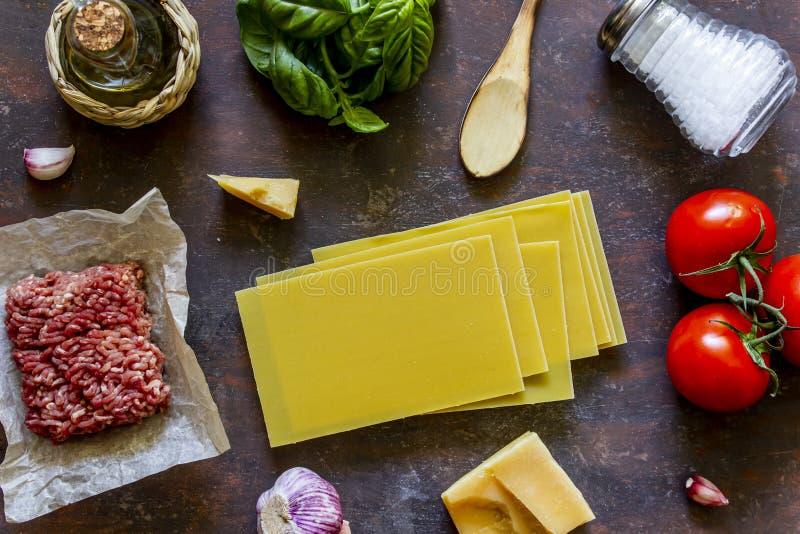 Lasa?as, tomates, carne picadita y otros ingredientes Fondo oscuro Cocina italiana fotografía de archivo