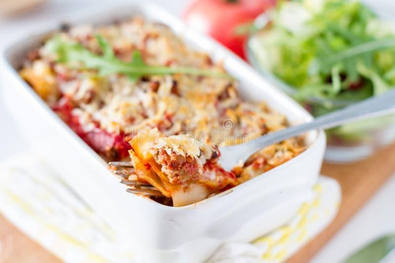 Lasagna που εξυπηρετείται στο άσπρο κύπελλο με τη σαλάτα στοκ εικόνα