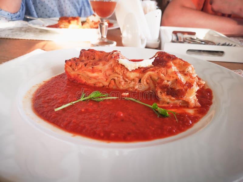 Lasagna στη σάλτσα ντοματών Νόστιμο εύγευστο ιταλικό lasagna πιάτων με τη σάλτσα ντοματών και τυρί κρέμας με το πράσινο salat Τρό στοκ φωτογραφία με δικαίωμα ελεύθερης χρήσης