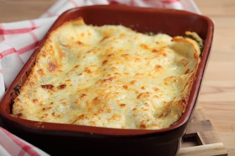 Lasagna in a baking dish. Lasagna with arugula in a baking dish royalty free stock images