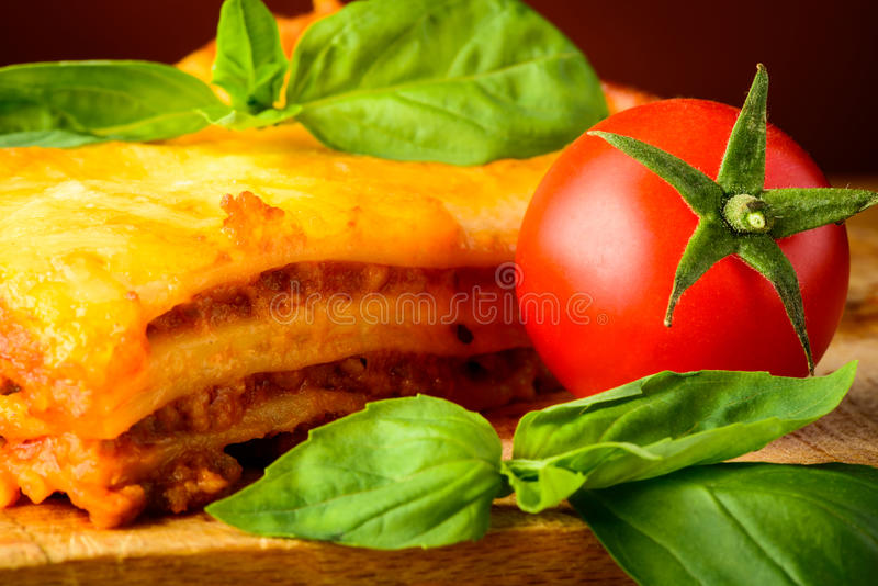 Lasagna bolognese, basil and tomato royalty free stock images