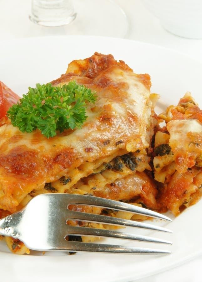 Lasagna con la fork en blanco imagen de archivo