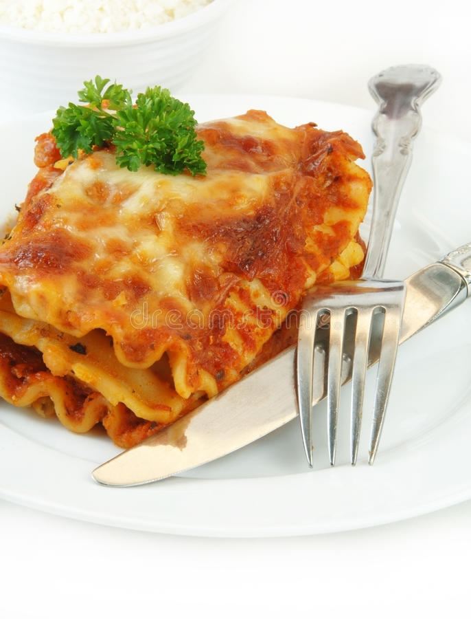 Lasagna con la fork y cuchillo en blanco imagen de archivo libre de regalías