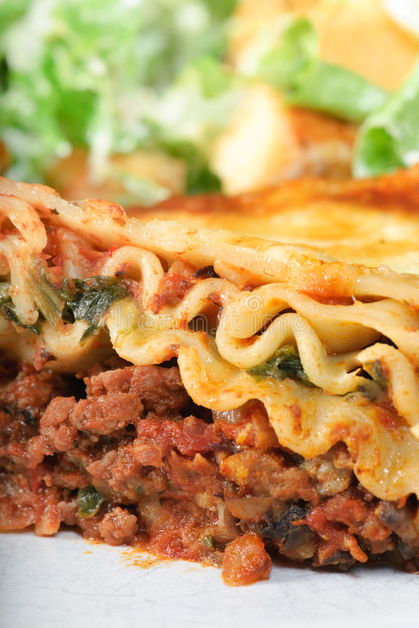 Lasagna Dinner. Spinach lasagna dinner with ceasar salad up close stock photography