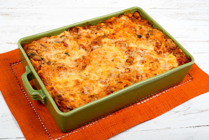 Lasagna in a green dish. Lasagna dish on orange towel stock photography