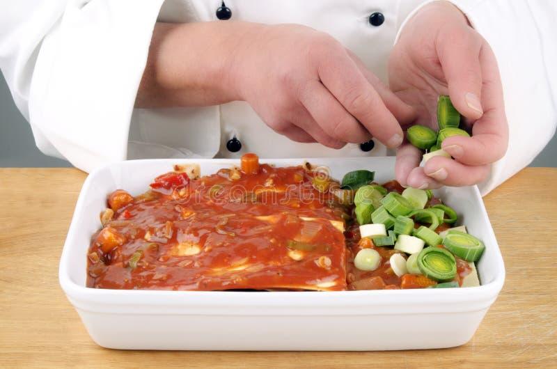 Lasagna preparado cozinheiro chefe com ââleek cortado imagem de stock royalty free