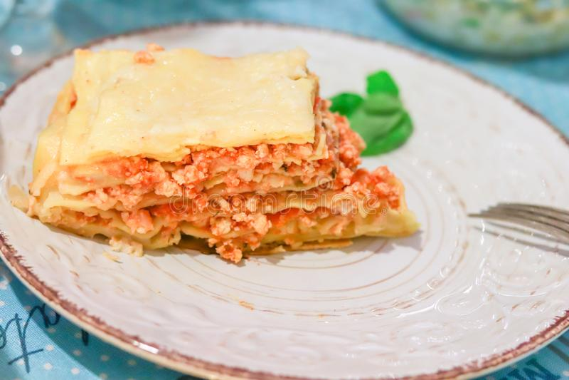 Lasagna's bolognese plak op een witte gevormde plaat met basilicum en vork op lijst stock foto's