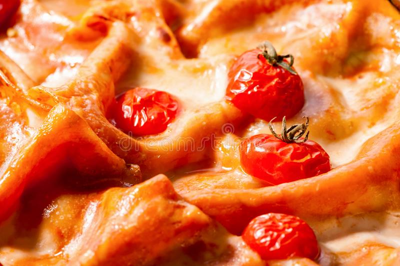 Lasagna surface with cherry tomatoes and melted cheese macro delicious food background stock image
