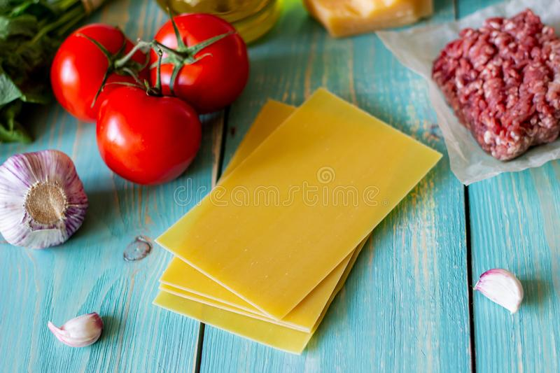 Lasagna, tomatoes, minced meat and other ingredients. Blue wooden background. Italian cuisine royalty free stock photography