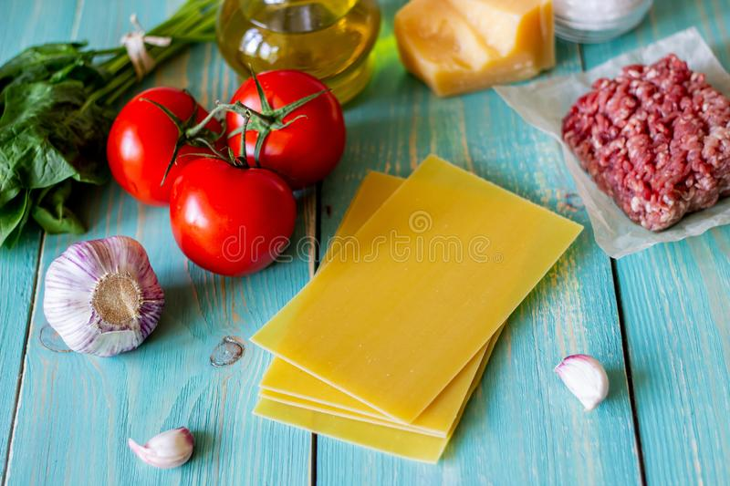 Lasagna, tomatoes, minced meat and other ingredients. Blue wooden background. Italian cuisine stock images
