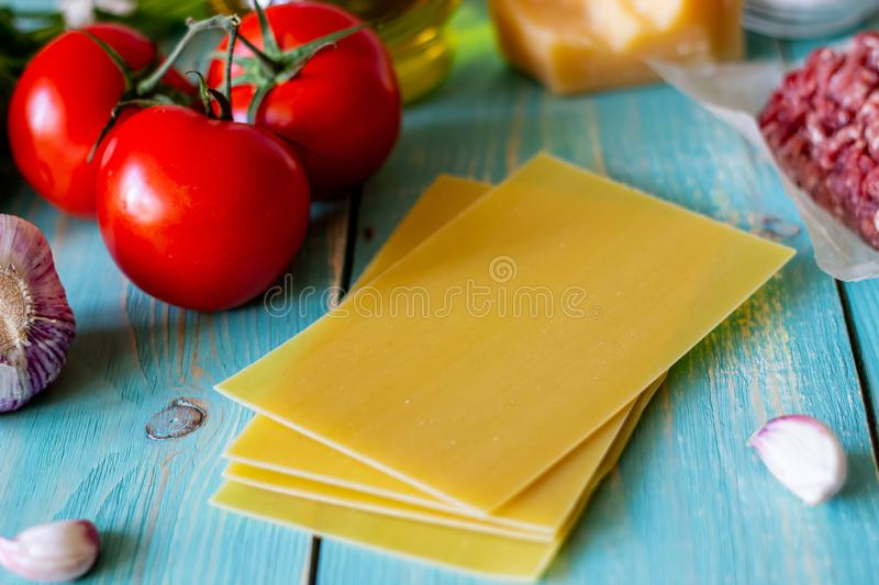 Lasagna, tomatoes, minced meat and other ingredients. Blue wooden background. Italian cuisine royalty free stock image