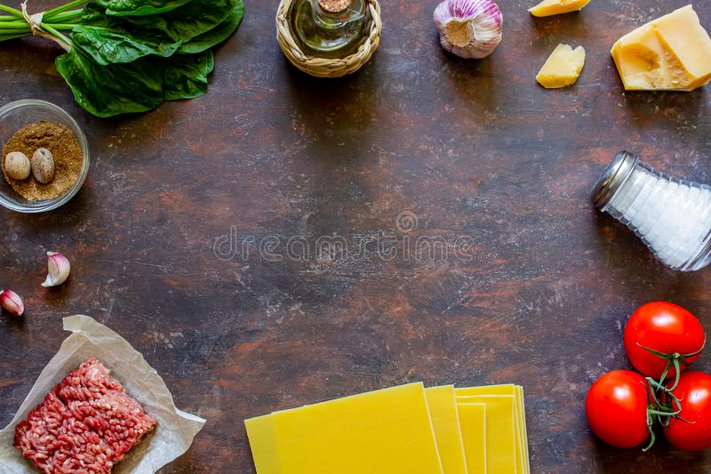 Lasagna, tomatoes, minced meat and other ingredients. Dark background. Italian cuisine royalty free stock photography
