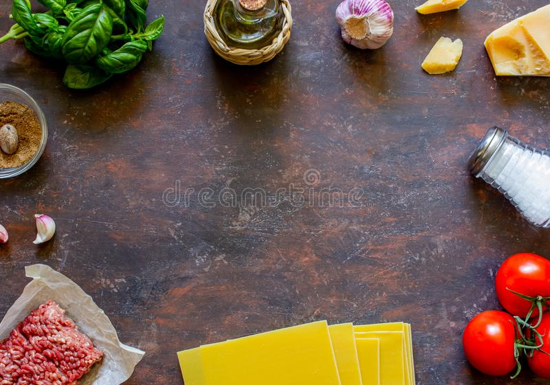 Lasagna, tomatoes, minced meat and other ingredients. Dark background. Italian cuisine stock photos