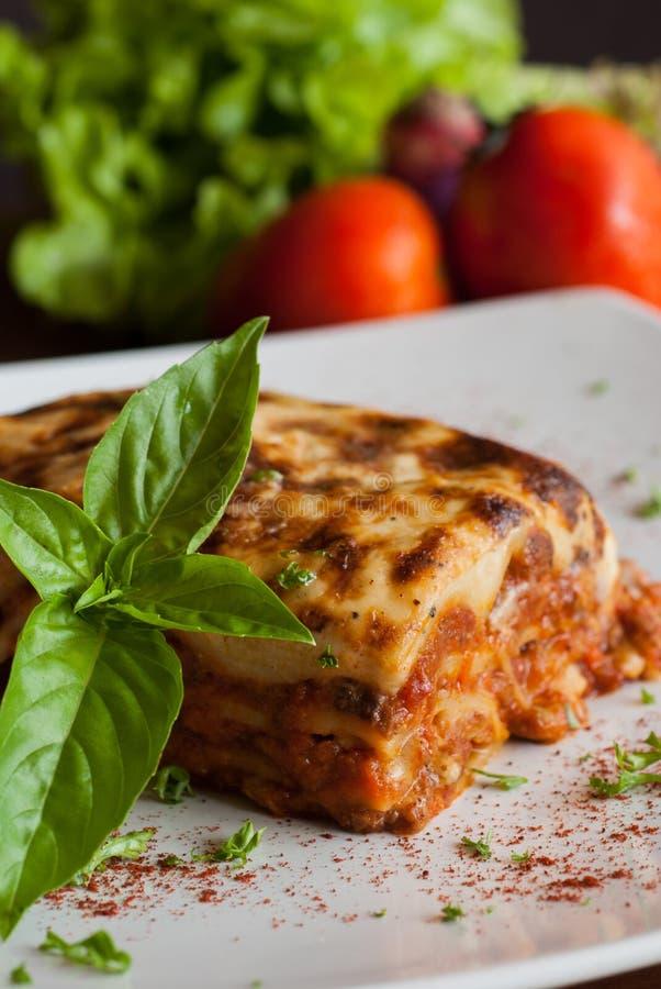 Lasagne al forno su un piatto bianco quadrato fotografia stock