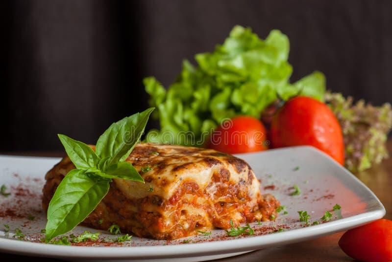 Lasagne al forno su un piatto bianco quadrato immagine stock