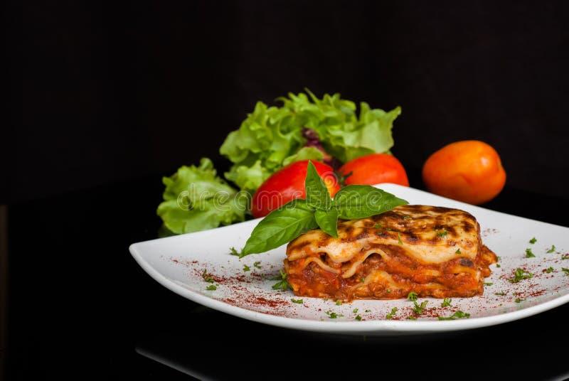 Lasagne al forno su un piatto bianco quadrato immagine stock libera da diritti