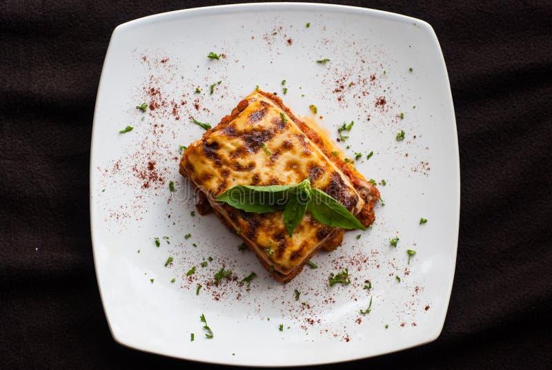 Lasagne al forno su un piatto bianco quadrato fotografia stock libera da diritti