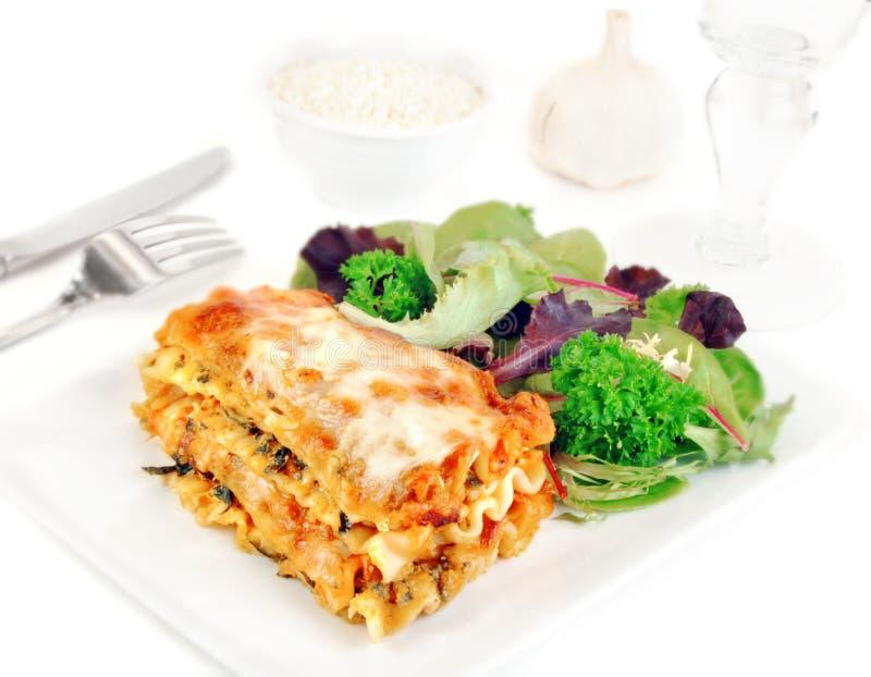 Lasagne auf einer Platte mit Salat stockfotografie