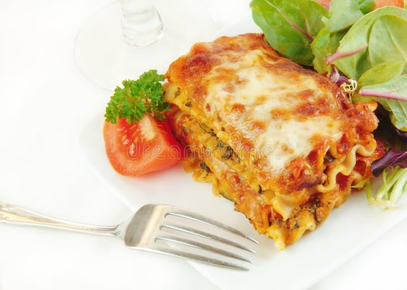 Lasagne auf einer Platte mit Salat lizenzfreies stockfoto