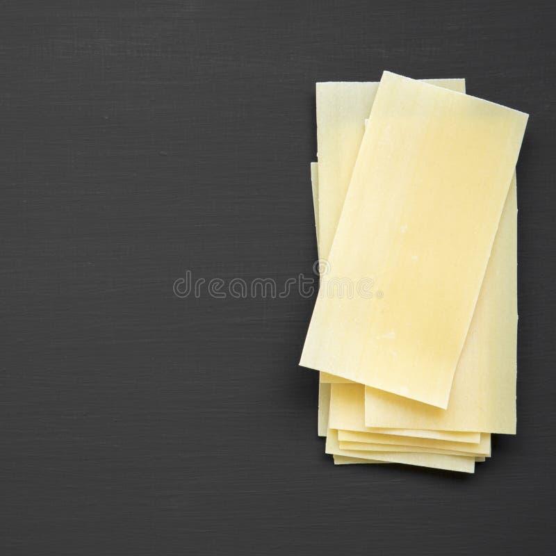 Lasagne bedeckt Teigwaren auf einem schwarzen Hintergrund, Draufsicht Von oben flache Lage, obenliegend lizenzfreie stockfotografie