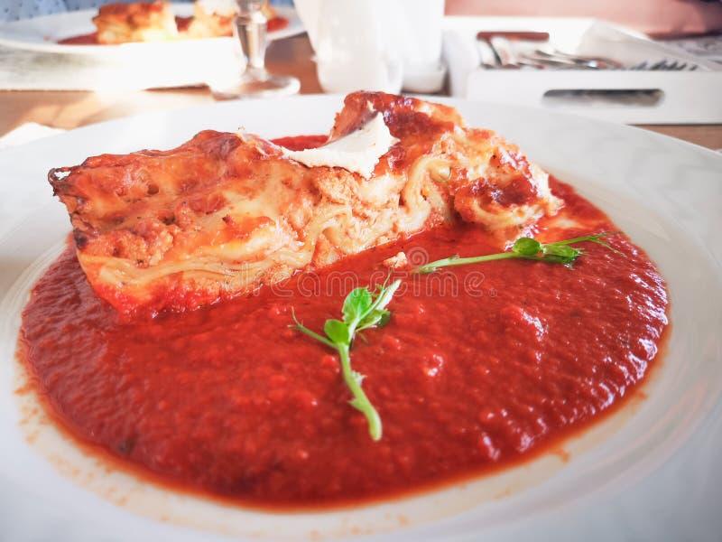 Lasagne in der Tomatensauce Geschmackvolle köstliche italienische Tellerlasagne mit Tomatensauce- und Frischkäse mit grünem salat lizenzfreie stockbilder
