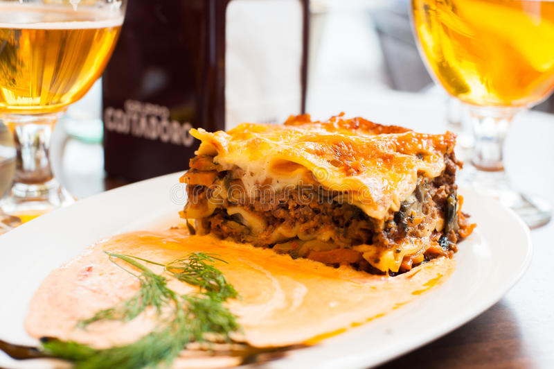 Lasagne food on the table. Glass of beer in background royalty free stock photos