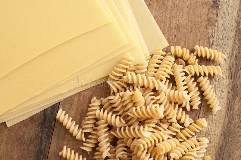 Lasagne with fusilli pasta on wooden background royalty free stock photography